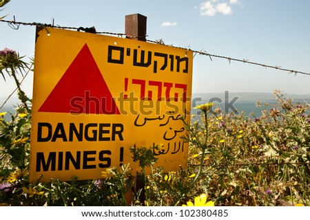 "A sign reading ""Danger Mines!"" hangs from a barbed wire fence in the Golan Heights. Effectively annexed by Israel in 1981, the Golan is still considered occupied territory under international law. - stock photo"