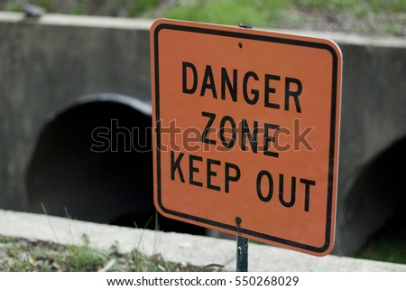 "A Sign Reads ""Danger Zone Keep Out"" Before a Steep Drop to a Culvert"