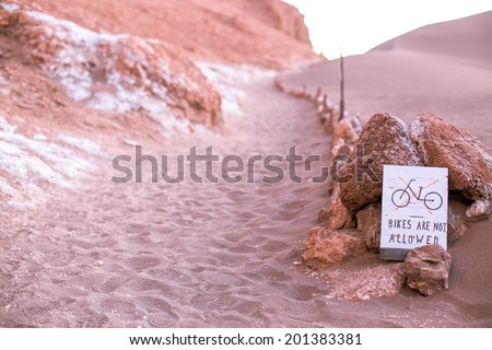 A sign says no bikes are allowed on the dune, moon valley, atacama desert  - stock photo