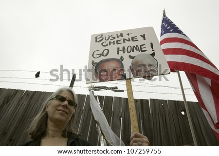 A sign shows President Bush and VP Cheney as the devil with the US Flag at an anti-Iraq War protest march in Santa Barbara, California on March 17, 2007 - stock photo