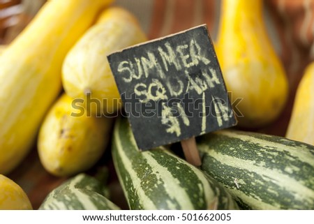 A sign shows summer squash on display at a market.