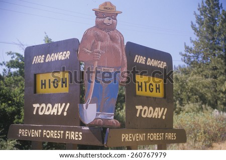 "A sign that reads ""?Fire danger high today"" with Smokey the bear - stock photo"