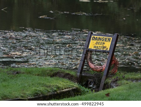 A sign warning of the danger of deep water nearby. A lifebuoy is attached to the sign.