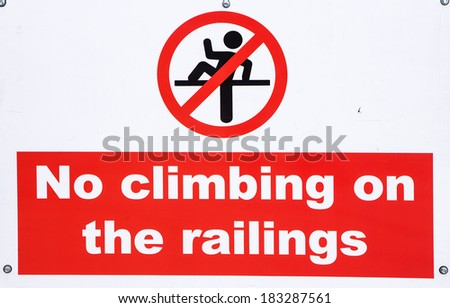 A sign warning people not to climb on the railings - stock photo