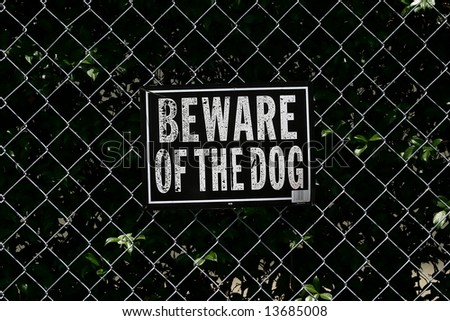 A sign warning the reader to beware of the dog, on a chain link fence backdrop. - stock photo