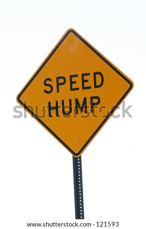 A sign warns of a speed hump ahead. - stock photo