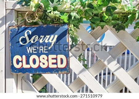 A sign written 'Sorry, we're closed' hanging on a white fence. - stock photo