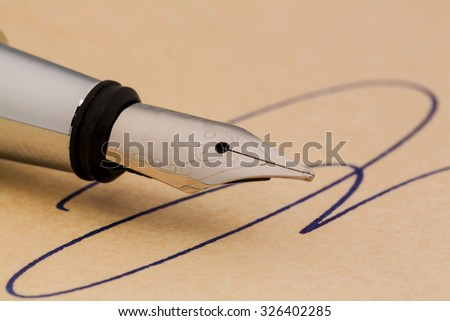 a signature and a fountain pen on yellow paper. symbolic photo for contract, testament and grafologie - stock photo