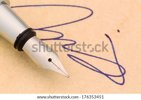 a signature and a fountain pen on yellow paper. symbolic photo for contract testament and graphology