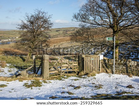 A signpost to a footpath through a wooden gate and across moorland in the South pennines close to Haworth in West Yorkshire - stock photo
