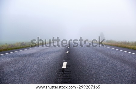 A silent asphalt road on a very foggy morning. Image taken during sunrise in Finland. - stock photo