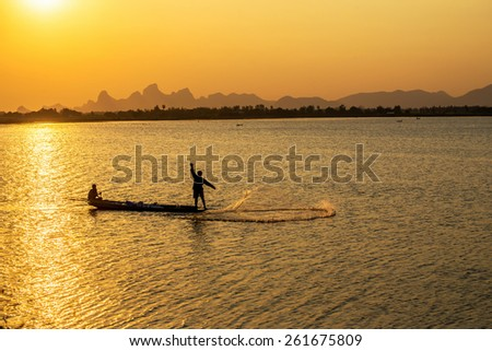 A silhouette fisherman throw a net to catch a fish in a river in the sunset time
