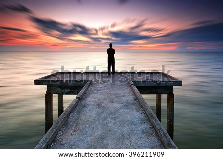 A silhouette man standing on the pier facing the sea during sunset. Long exposure sky effect.... - stock photo