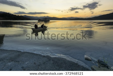 A  silhouette motion fisherman boat cruise the lake during sunset (motion blur) - stock photo