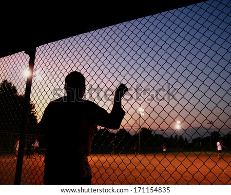 a silhouette of a baseball/softball player in the dugout - stock photo
