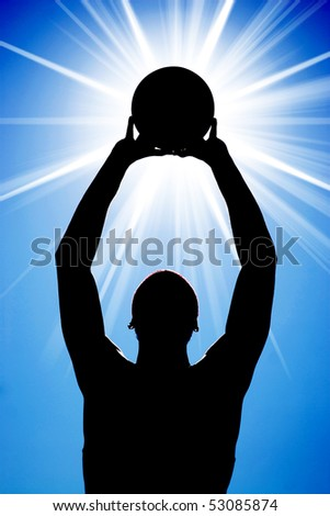 A silhouette of a basketball player holding up a ball in front of a bright glowing lens flare. - stock photo