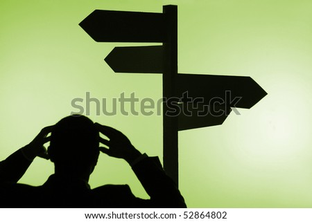 A silhouette of a businessman, confused about which direction to go. - stock photo