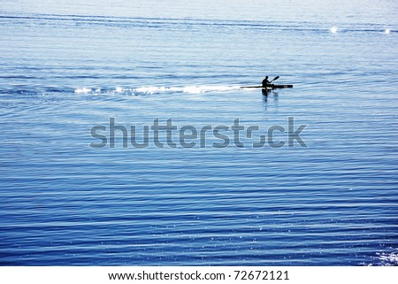 a silhouette of a canoe rower practicing on a lake. - stock photo