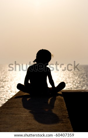 A silhouette of a child on the beach