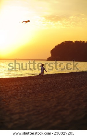 A silhouette of a child running with a kite along the sea coast against the sunset sky on a warm summer evening - stock photo