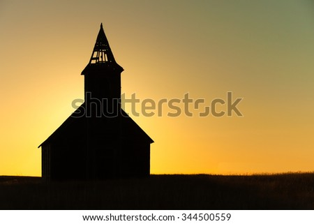 A silhouette of a church steeple at sunset. - stock photo