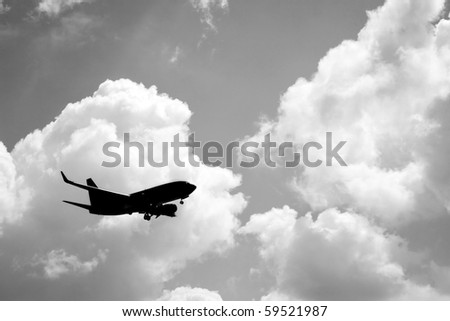 A silhouette of a commercial passenger plane over partly cloudy sky in its descent to land. - stock photo