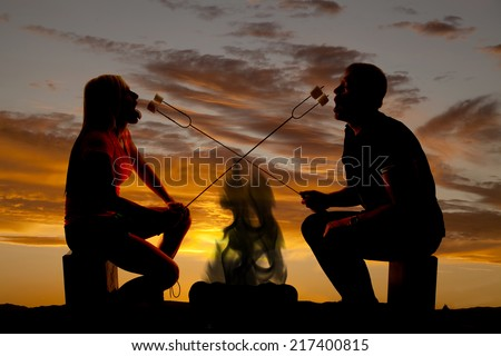 A silhouette of a couple in the outdoors roasting marshmallows over a fire. - stock photo