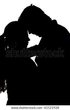 A silhouette of a couple with their heads together. - stock photo