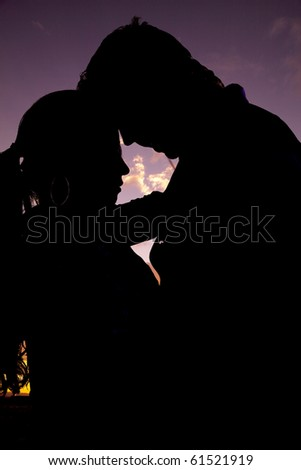A silhouette of a couple with their heads together with a beautiful background. - stock photo