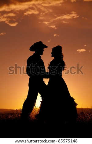 A silhouette of a cowboy and a woman dancing in the sunset. - stock photo