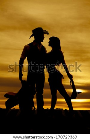 A silhouette of a cowboy and an indian in front of a sunset. - stock photo