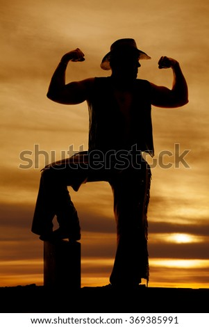 A silhouette of a cowboy flexing his arms in his western clothing with his foot on a log. - stock photo