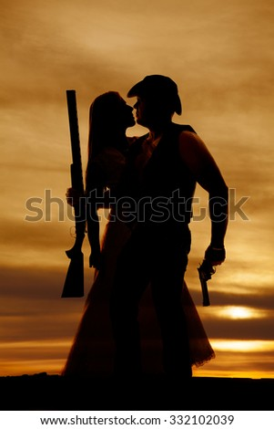 A silhouette of a cowboy holding his lady close, while he holds his guns. - stock photo