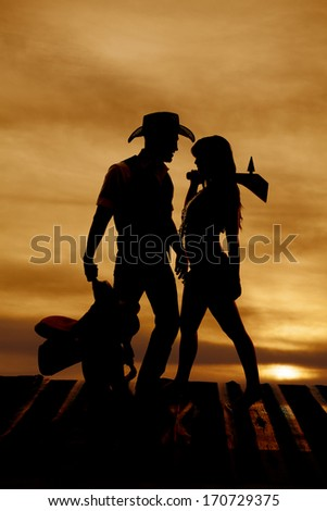 A silhouette of a cowboy holding his saddle and an Indian holding her club. - stock photo