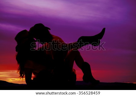 a silhouette of a cowboy holding on to his cowgirl. - stock photo