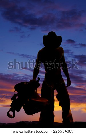 a silhouette of a cowboy holding on to his saddle looking down. - stock photo