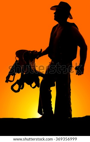 A silhouette of a cowboy holding on to his saddle looking off.