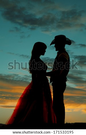 a silhouette of a cowboy holding onto his beautiful woman. - stock photo