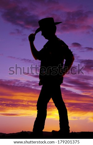 A silhouette of a cowboy holding the front of his hat. - stock photo