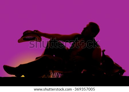 A silhouette of a cowboy leaning back on a saddle resting. - stock photo