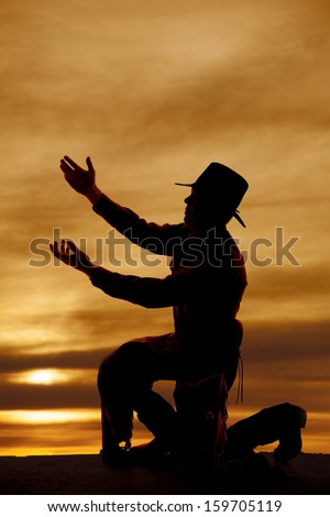 A silhouette of a cowboy on his knee with arms up. - stock photo