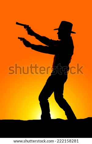a silhouette of a cowboy pointing two pistols to the side. - stock photo