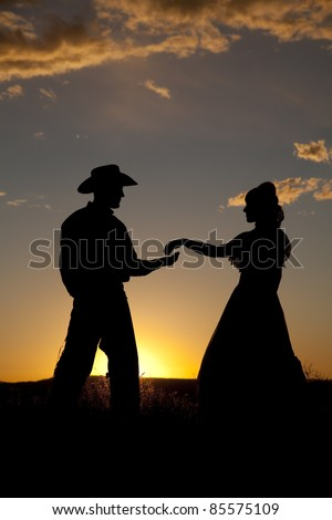 A silhouette of a cowboy reaching out for a woman's hand in the sunset.