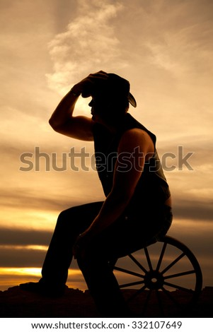 A silhouette of a cowboy sitting on a wagon wheel with his hand on his hat. - stock photo