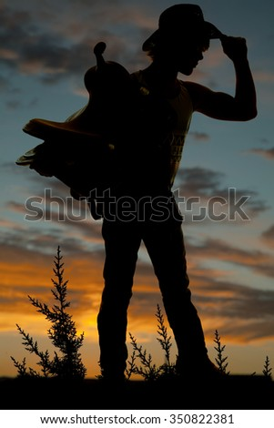 a silhouette of a cowboy touching the brim of his hat, and holding on to his saddle. - stock photo