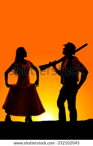 A silhouette of a cowboy with a gun on his shoulder and his lady coming towards him. - stock photo