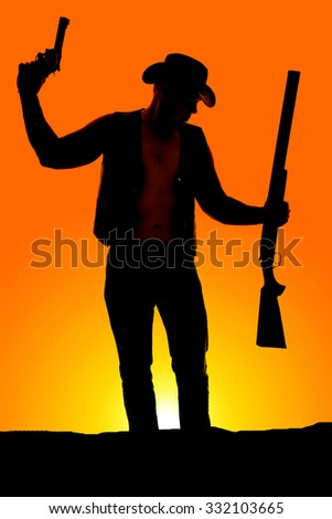 a silhouette of a cowboy with a pistol and shotgun in his hands. - stock photo
