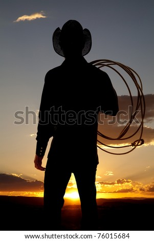 A silhouette of a cowboy with a rope on his shoulder in the sunset. - stock photo
