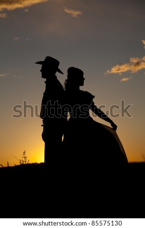 A silhouette of a cowboy with his back to a woman in the sunset. - stock photo