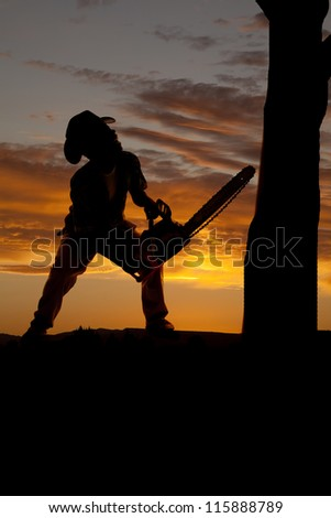 A silhouette of a cowboy with his chainsaw getting ready to cut down a tree.